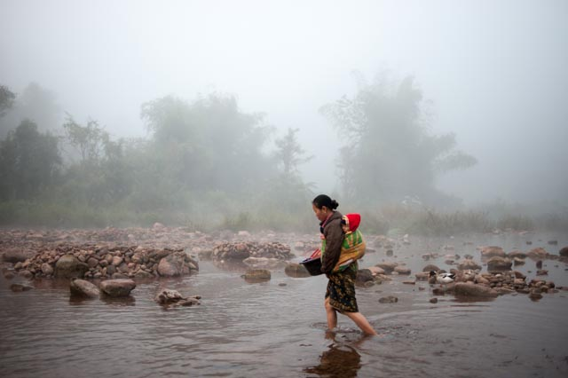 A woman and child head into the river for a morning wash