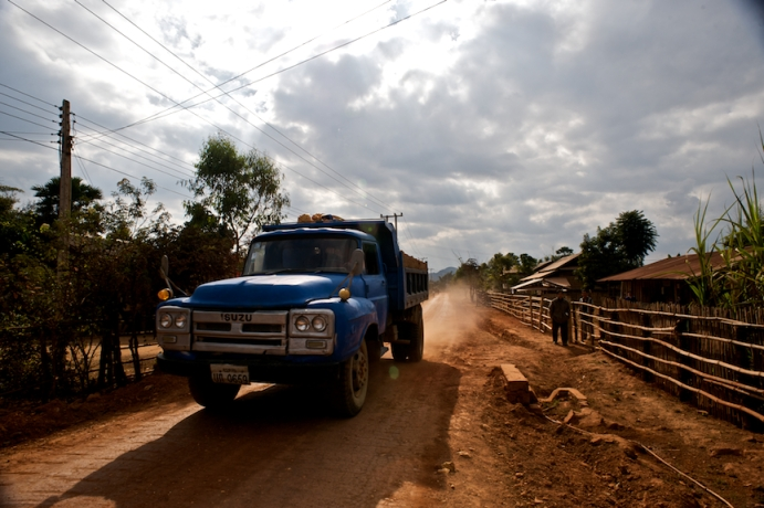 A truck rumbles by on a dirt road, near Phonsavan