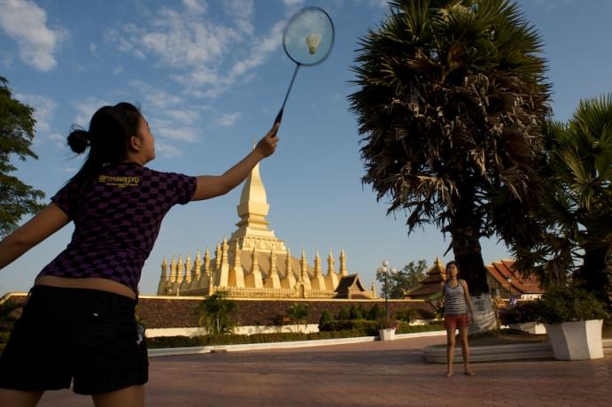 Women play a game of badminton near Pha That Luang