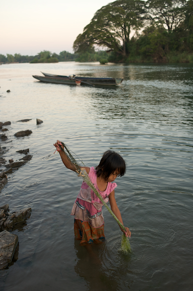 A young girl checks her net for fish in the Mekong