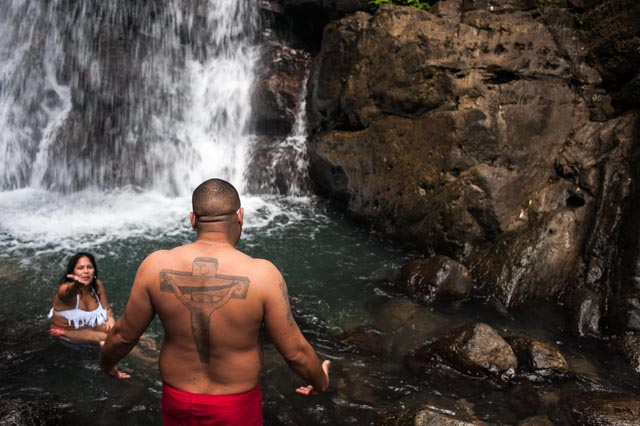 A woman encourages her friend to take a plunge at the La Mina Falls in the Yunque Rain Forest