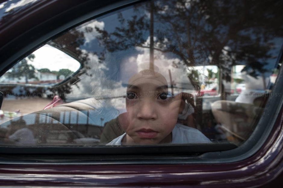 A young girl looks out the window of her family's car as it makes its way down the parade route